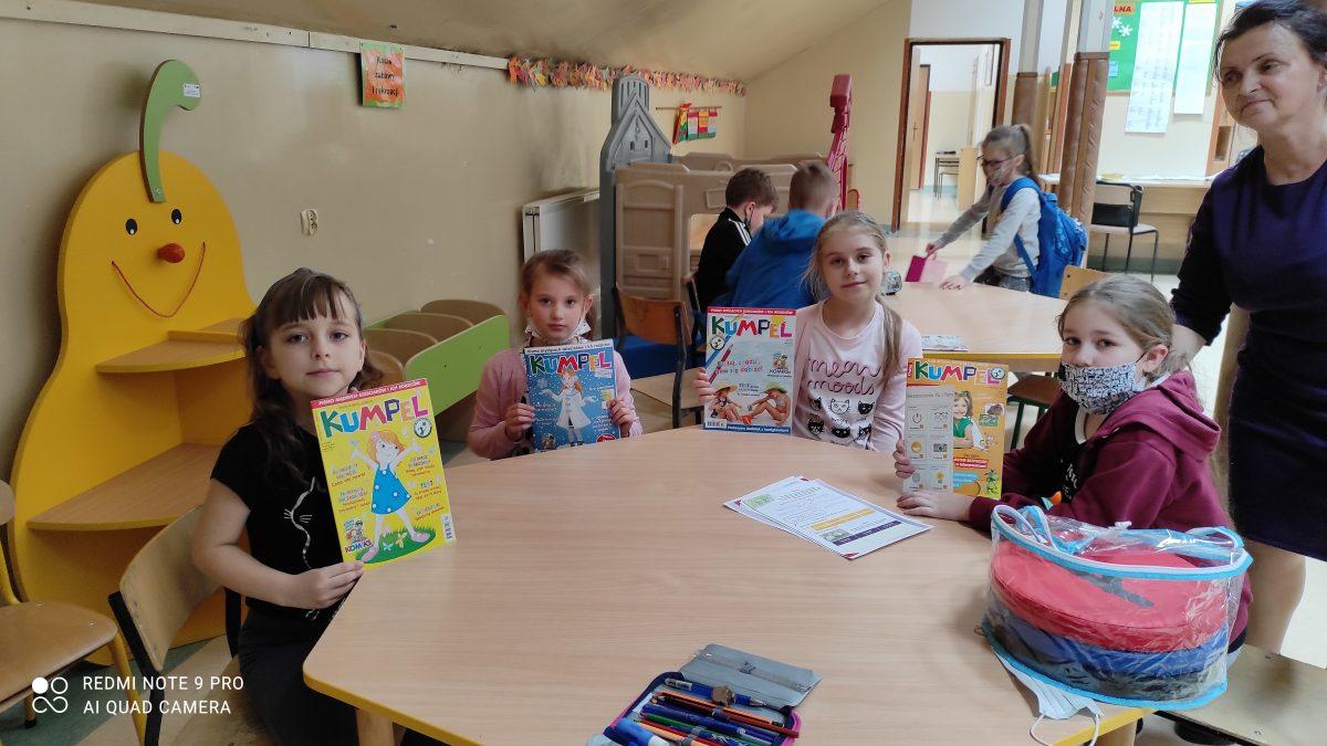 Dzieci przy stole z czasopismami